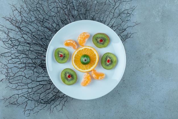 Fruitsalade met gehakte en gesneden kiwi's, mandarijn en sinaasappels.