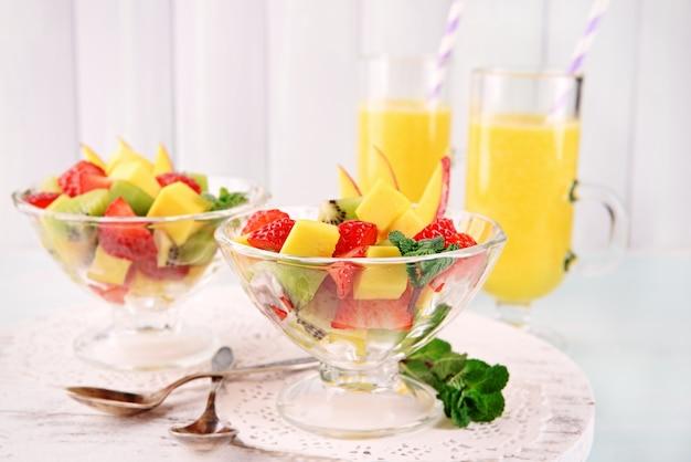 Fruitsalade met munt en jus d'orange in glaswerk op houten tafel en planken