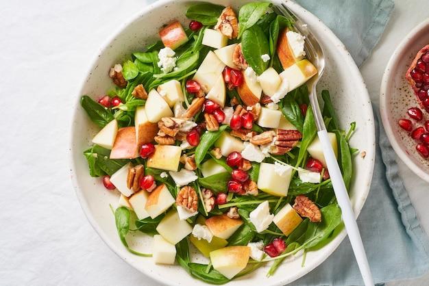 Fruitsalade met noten, uitgebalanceerd voedsel, schoon eten. spinazie met appels, pecannoten en feta, gegarneerd met granaatappelpitjes in kom op tafel met wit tafellaken.