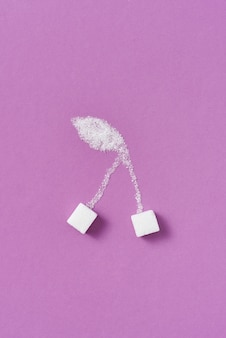 Fruitsamenstelling handgemaakt van zoete geperste en gekorrelde zoete suiker kersenbessen op een paarse muur met kopie ruimte. plat leggen.