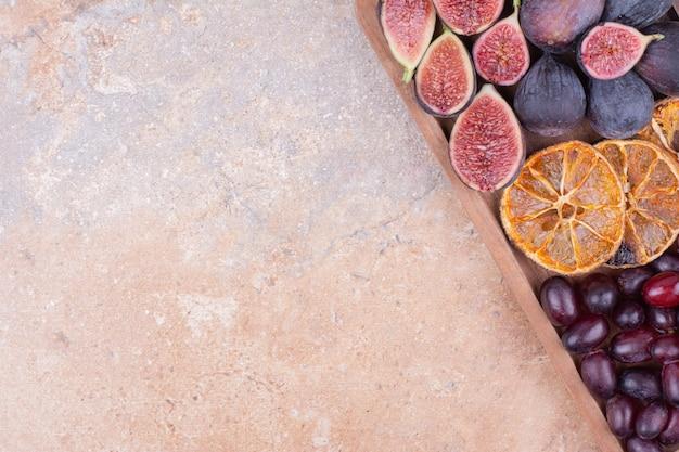 Fruitschaal met cornels, vijgen en stukjes sinaasappel