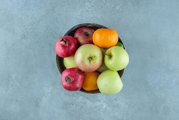 Fruitschaal met granaatappels, appels en mandarijnen.