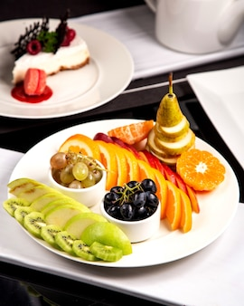 Fruitschaal met sinaasappel en peer van de kiwi de groene appeldruiven
