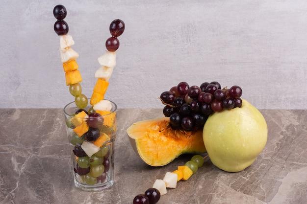 Fruitstokken en vers fruit op marmeren oppervlak.