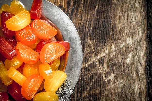 Fruitsuikergoed op een stalen dienblad. op een houten achtergrond.