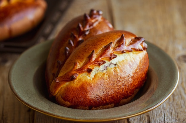 Fruittaart uit de oven bakdag zoet gebak met kersen traditioneel russisch gebak russisch broodje met bessen pirozhki met kersen close-up van gebakken goederen uit de oven taart food day