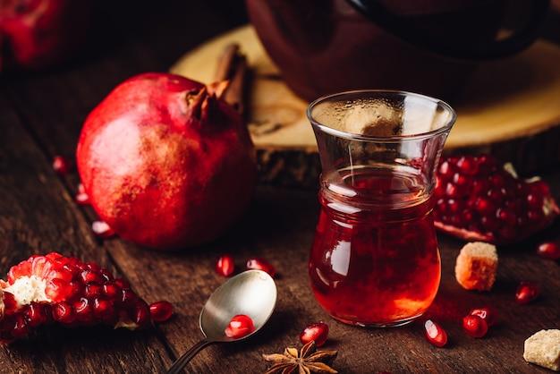 Fruitthee in armudu glas met verse granaatappel en wat kruiden