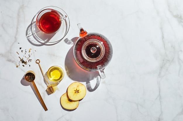 Fruitthee met appels en tijm en honing in glazen theepot en kopje and
