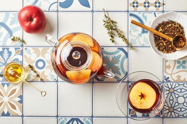 Fruitthee met appels en tijm in glazen theepot en kopje op tafel gemaakt van gekleurde tegels