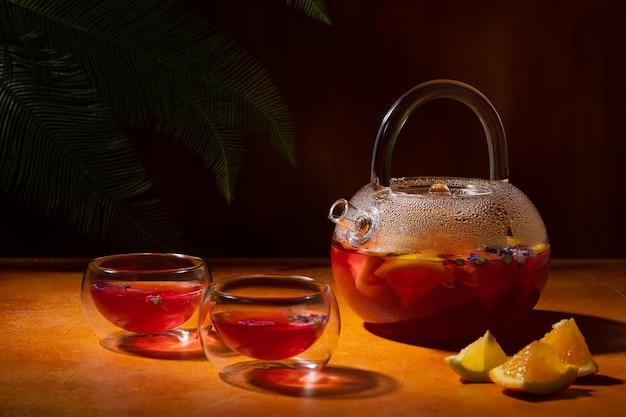 Fruitthee met sinaasappel-citroen droge kaasjeskruid bloemen in glazen theepot en twee kommen op oranje muur