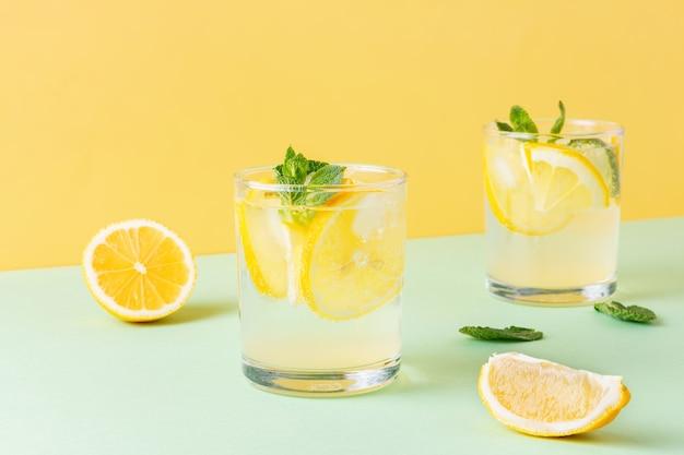 Fruitwater met citroen en muntblaadjes op gecombineerde gele en groene achtergrond. twee glazen koele koolzuurhoudende cocktail met citrus.