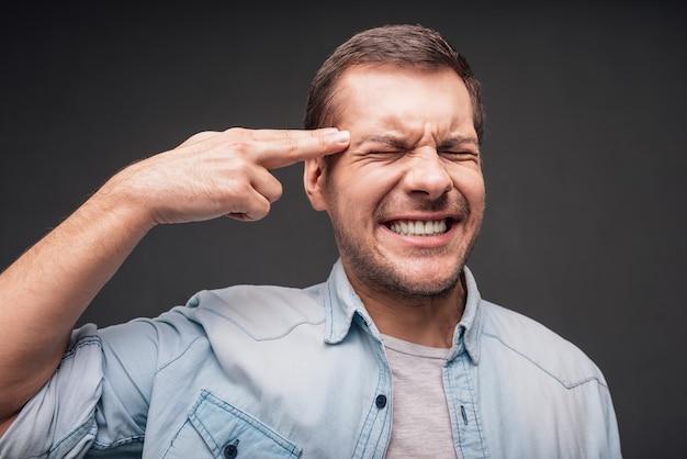 Frustratie en wanhoop. close-up van een knappe jongeman die een handgeweer maakt en zijn ogen gesloten houdt terwijl hij tegen een grijze achtergrond staat