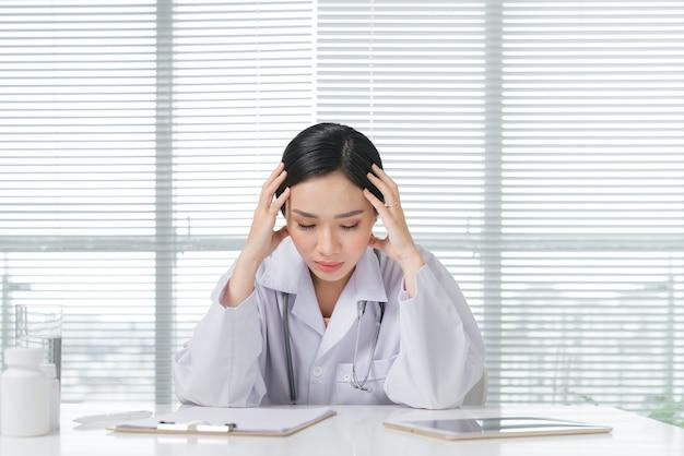 Frustratie jonge vrouwelijke arts die in haar spreekkamer zit