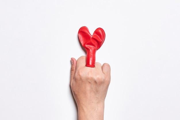Fuck liefde middelvinger en hartvormige ballon hand van persoon die fuck handgebaar over wit laat zien