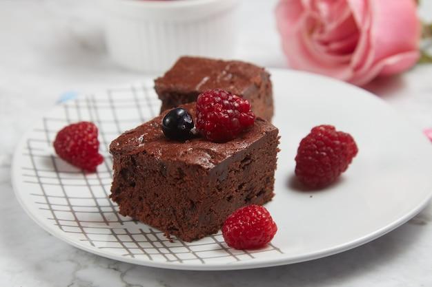 Fudgy brownie met bessen op witte marmeren achtergrond.