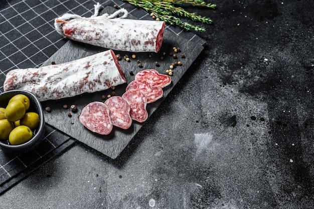 Fuet salami in plakjes gesneden en rozemarijn. traditionele spaanse worst. zwarte achtergrond. bovenaanzicht. ruimte voor tekst