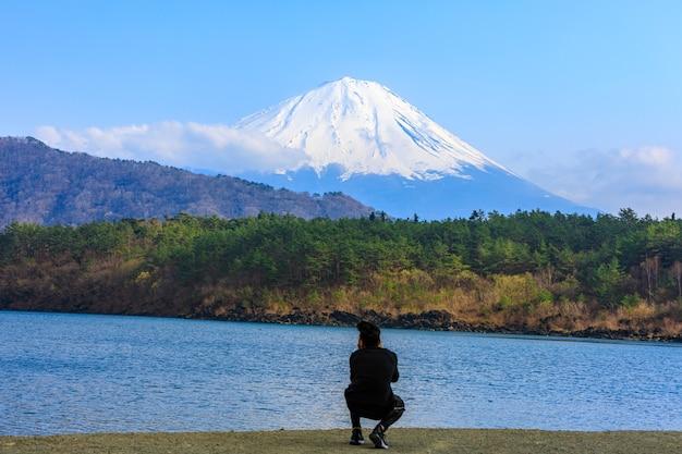 Fuji-berg en rivierbos voorgrond en reistoerist neemt foto met smartphone in japan