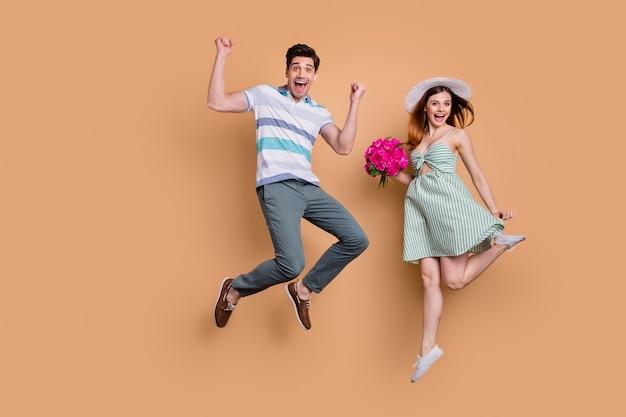 Full body aantrekkelijke dame knappe jongen opgewonden paar sprong houden bos bloemen
