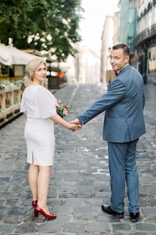 Full body achteraanzicht portret van volwassen gelukkig stel, gekleed in luxe elegante kleding, wandelen op straat in de stad, een date of huwelijksverjaardag vieren