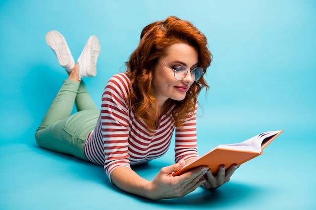 Full body close-up foto van positieve meisje liggend vloer gedichten lezen geniet van rust ontspannen draag goed kijken jumper geïsoleerd over blauwe kleur