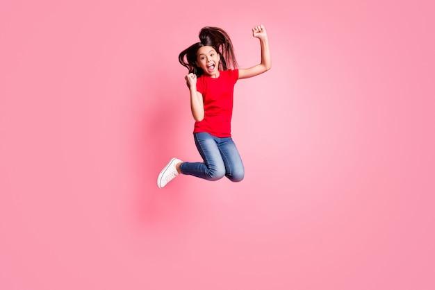 Full body foto van extatische jongen meisje springen vuisten dragen rode t-shirt jeans geïsoleerd over pastelkleurige achtergrond
