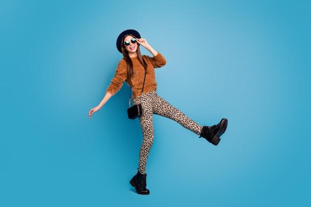Full body foto van funky gek meisje geniet van wintervakantie wandeling voel inhoud draag goed uitziende outfit geïsoleerd over blauwe kleur muur