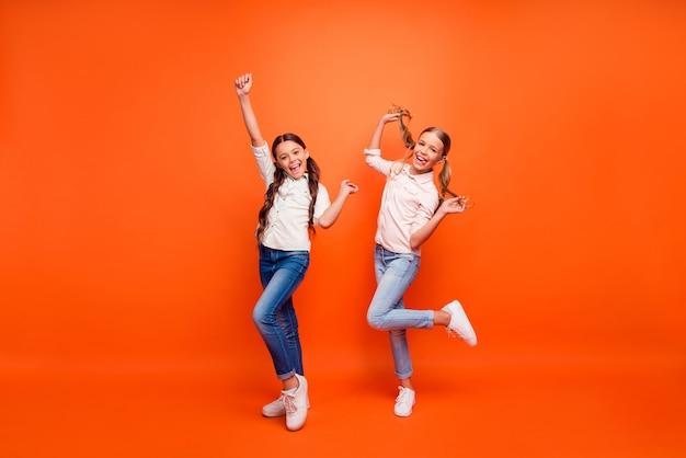 Full body foto van funky gekke twee vriendinnen hebben plezier in herfstweekends handen opsteken vuisten houden armen vlechten dragen wit overhemd sneakers geïsoleerde oranje kleur achtergrond