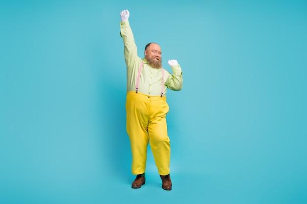 Full body foto van funky man dansen op blauwe achtergrond