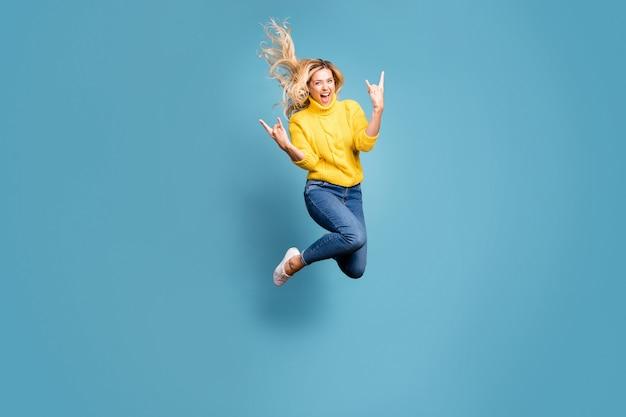 Full body foto van gekke dame hoog springen genieten van metal rock concert tonen handen hoorns opgewonden slijtage gebreide gele trui jeans geïsoleerde blauwe kleur muur