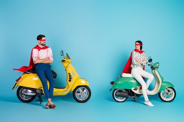 Full body foto van grappige coole dame kerel armen gekruist zitten twee vintage bromfiets slijtage rode cape masker klaar voor halloween feest spelen superhelden rol geïsoleerde blauwe kleur muur