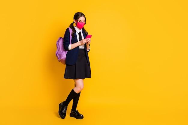 Full body foto van high student blogger girl gebruikt smartphone