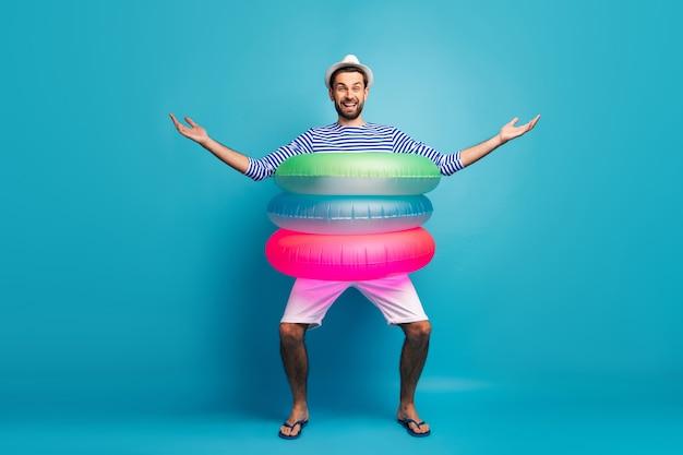 Full body foto van knappe kerel reiziger stapt binnen drie kleurrijke rubberen reddingsboeien gaan zwemmen zwembad zee oceaan dragen gestreepte matroos shirt pet korte broek flip flops geïsoleerde blauwe kleur