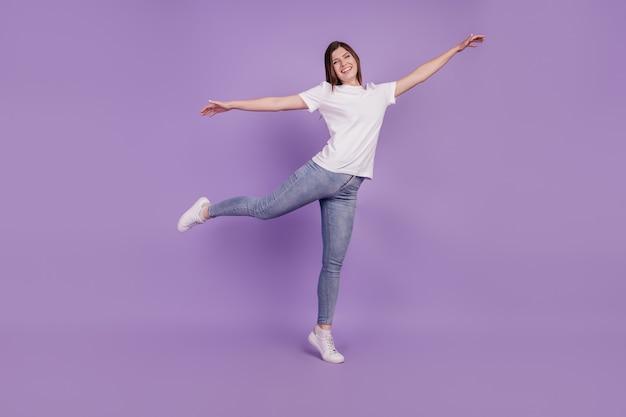 Full body foto van meisje hand in hand vliegtuigen outfit geïsoleerd over paarse achtergrond