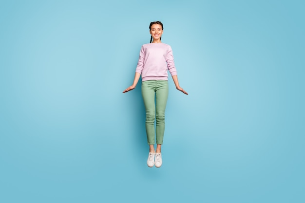 Full body foto van mooie dame hoog springen genieten van geweldige zonnige lentedag weer vreugde goed humeur dragen casual roze trui groene broek geïsoleerde blauwe kleur