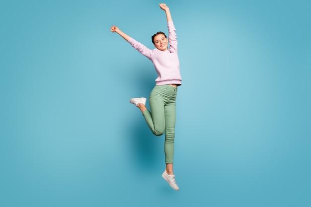 Full body foto van mooie dame hoog springen genieten van verbazingwekkende zonnige lentedag weer handen opsteken verheugend dragen casual roze trui groene broek geïsoleerde blauwe kleur