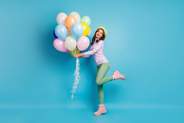 Full body foto van mooie grappige dame brengen veel kleurrijke luchtballonnen vrienden evenement feestkleding paarse trui baret pet groene broek schoenen geïsoleerde blauwe kleur muur