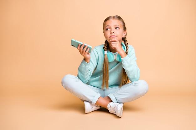 Full body foto van mooie kleine dame luisteren koptelefoon lied zitten vloer benen gekruist saai les school wachten naar huis gaan dragen blauwe trui jeans schoeisel geïsoleerde beige kleur muur