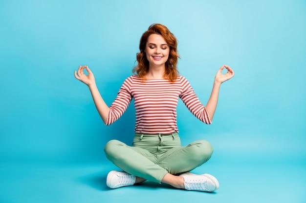 Full body foto van positieve rustige vrouw zitten gekruiste benen mediteren yoga show om symbool dragen witte schoenen outfit geïsoleerd over blauwe kleur