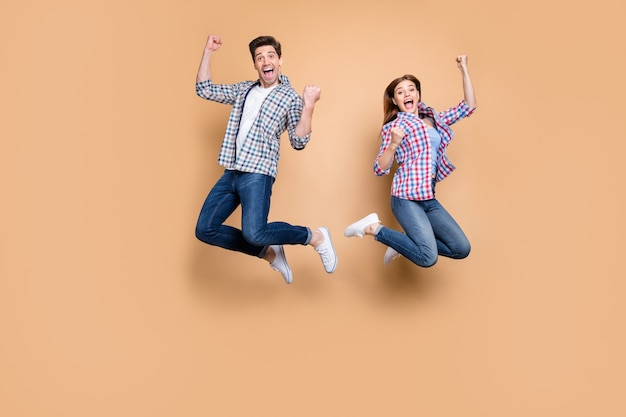 Full body foto van twee mensen gekke dame kerel springen hoog vieren beste overwinning verhogen vuisten verkoop winkelen nieuws slijtage casual geruite jeans kleding geïsoleerde beige achtergrond