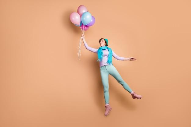 Full body foto van vrij geschokte dame hoog springen houden veel lucht ballonnen opstaan met wind klap slijtage violet trui groene broek laarzen blauwe baret sjaal geïsoleerde beige kleur achtergrond