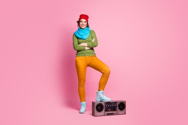 Full body foto vrolijk zelfverzekerd hipster meisje zet haar schoenen retro boom doos kruis handen klaar rock feestkleding blauw rood hoofddeksels groen geel trui broek geïsoleerde roze kleur muur