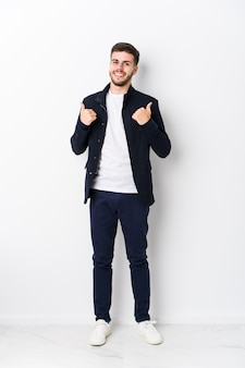 Full body jonge blanke man verhogen beide duimen omhoog, glimlachen en zelfverzekerd.