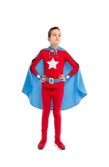 Full body jongen in rood en blauw superheld kostuum hand in hand op taille en wegkijken tegen wit
