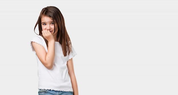 Full body klein meisje bijt nagels, nerveus en erg angstig en bang voor de toekomst, voelt paniek en stress