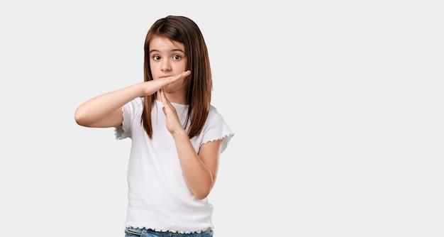 Full body klein meisje moe en verveeld, het maken van een time-out gebaar