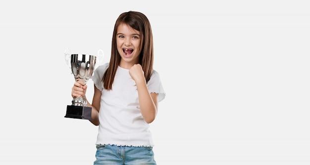 Full body klein meisje opgewonden en energiek, het verhogen van een glas na het behalen van een moeilijke overwinning, beloning voor hard werken, zelfverzekerd en positief