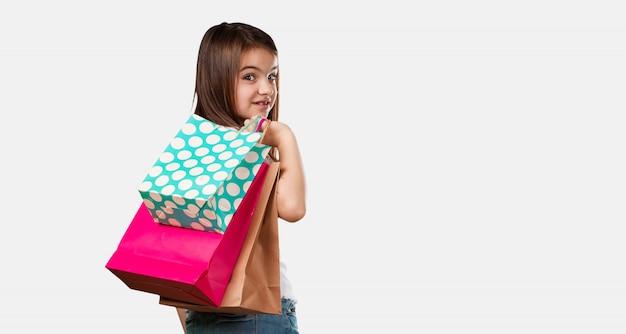 Full body klein meisje vrolijk en lachend, erg enthousiast met een boodschappentas, klaar om te gaan winkelen en op zoek naar nieuwe aanbiedingen