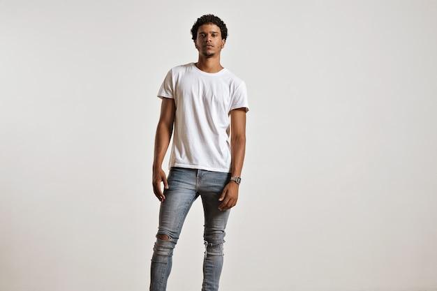 Full-body portret van een atletische jonge man in gescheurde lichtblauwe spijkerbroek en lege witte shortsleeve t-shirt