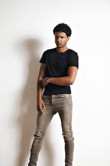 Full body portret van een boos uitziende fronsende zwarte jonge man in een effen zwart t-shirt en magere grijze spijkerbroek geïsoleerd op wit