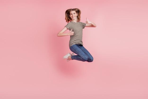 Full body portret van jonge vrouw gelukkig positieve glimlach tonen duim omhoog als prima keuze advertentie springen geïsoleerd over roze kleur achtergrond